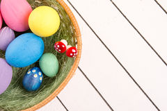 Colorful ecological styrofoam Easter eggs in basket on a wooden background Royalty Free Stock Image