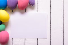 Colorful ecological styrofoam Easter eggs and blank white sheet of wood background Royalty Free Stock Images