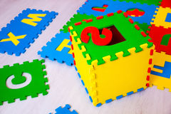 Colorful educational rugs for kids jigsaw puzzles, which are fashionable to collect in the boxes with the English alphabet, teach Stock Images