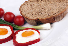 Colorful egg breakfast. Cooked breakfast with fried eggs in pepper rings, sliced bread, tomato and spring onion stock photo