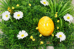Colorful egg. S lie on a synthetic grass and flowers Stock Images