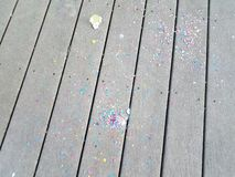 Colorful egg shells and paper confetti on wood deck. Colorful cracked egg shells and paper confetti on wood deck stock image