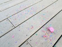 Colorful egg shells and paper confetti on wood deck. Colorful cracked egg shells and paper confetti on wood deck royalty free stock images