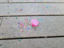 Colorful egg shells and paper confetti on wood deck. Colorful cracked egg shells and paper confetti on wood deck stock photo