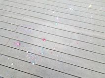 Colorful egg shells and paper confetti on wood deck. Colorful cracked egg shells and paper confetti on wood deck stock images