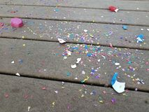 Colorful egg shells and paper confetti on wood deck. Colorful cracked egg shells and paper confetti on wood deck stock photos