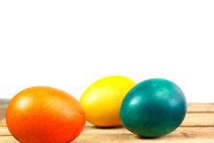 Colorful eggs. Easter eggs on wooden floor over white background Stock Photos