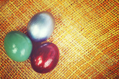 Colorful eggs on bamboo weave sheet background, Vintage style image. Stock Photos