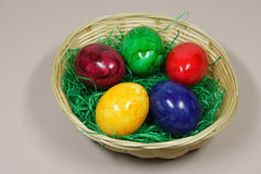 Colorful eggs in a basket. With green grass royalty free stock image