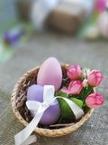 Colorful eggs with bowknot and spring flowers in basket on burlap background. Easter eggs with bowknot and decorative roses in basket on burlap surface royalty free stock photos