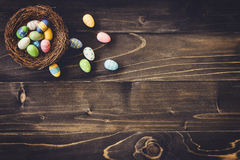 Colorful eggs easter in the nest on wood background with copyspa Stock Photo