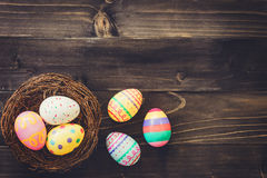 Colorful eggs easter in the nest on wood background with copyspa Stock Images