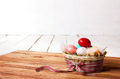 Colorful eggs and feathers  in  basket Stock Photos