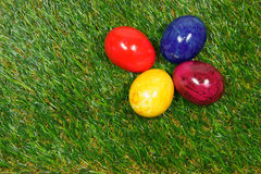 Colorful eggs. Four colorful eggs lie on a synthetic grass stock images