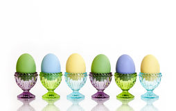 Colorful Eggs in Glass Eggcups. Six colored eggs in colorful glass eggcups on white reflective surface and white background Royalty Free Stock Photos