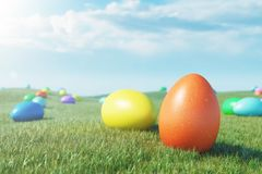 Colorful eggs in a meadow on a sunny day against the blue sky. Multicolored painted easter eggs on grass, lawn. Concept royalty free stock photography