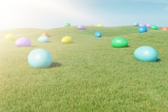 Colorful eggs in a meadow on a sunny day against the blue sky. Multicolored painted easter eggs on grass, lawn. Concept royalty free stock image