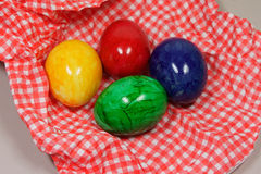 Colorful eggs on a napkin. Colorful eggs on a red and white napkin royalty free stock images