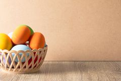 Colorful eggs are placed in a basket on a wooden table royalty free stock image