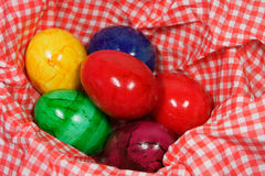 Colorful eggs in a red and white napkin. Six colorful easter eggs in a red and white napkin royalty free stock photo