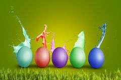 Colorful eggs with splashing paint. Five easter eggs in a row with liquid paint splashing around them. green colored background and a bit of grass in the Stock Photo