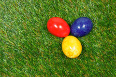 Colorful eggs. Three colorful easter eggs lie on a synthetic grass royalty free stock photos