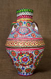 Colorful Egyptian handcrafted artistic ornate pottery jar on sackcloth background Stock Photography