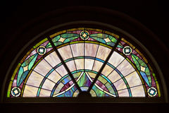 Colorful, elegant patterned stained glass window in circle top design. Stock Photo