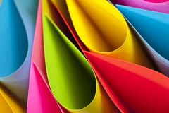 Colorful Ellipses. Macro and abstract image of colored cardstock (blue,red,pink,yellow and green) with an elliptical shape on a black background. Selective focus royalty free stock photos