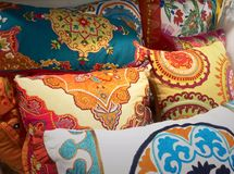 Colorful embroidered Indian pillows. An assortment of eclectic, decorator throw pillows, with embroidered details and ethnic themes. Vibrant brightly colored Stock Photo