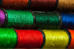 Colorful embroidery threads. Colorful embroidery thread bobbins arranged in rows Stock Photos