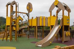 Colorful empty playground in park. Yellow and brown fun park for children. stock photo