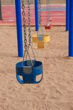 Colorful Empty Swings in Sand Stock Images