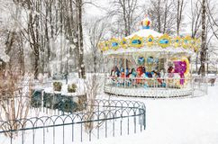 Empty vintage carousel in the park on snowy winter day Stock Photos