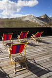 Colorful empy deckchairs on terrace with Italian Alps mountains Stock Image