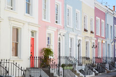 Colorful English houses facades, pastel pale colors. In London stock images