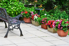 Colorful English patio area with planters and iron bench. Stock Image