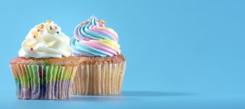 Colorful and enteresting cupcake isolated on blue background studio close up shot. Colorful and enteresting cupcake isolated on blue background studio close up royalty free stock photo