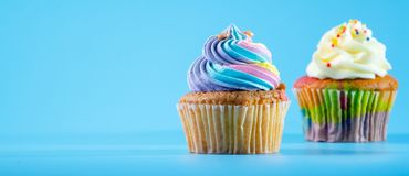 Colorful and enteresting cupcake isolated on blue background studio close up shot. Colorful and enteresting cupcake isolated on blue background studio close up royalty free stock photography