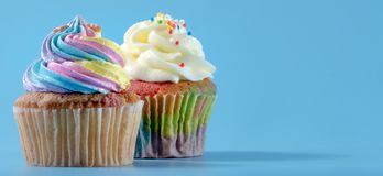 Colorful and enteresting cupcake isolated on blue background studio close up shot. Colorful and enteresting cupcake isolated on blue background studio close up stock image