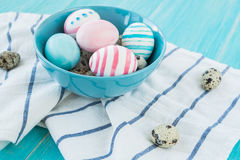 Colorful equal and chicken Easter Eggs on the blue rustic wooden background with towel. Selective focus. Royalty Free Stock Photography