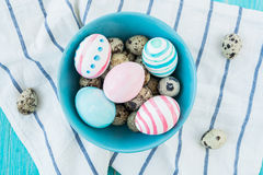 Colorful equal and chicken Easter Eggs on the blue rustic wooden background with towel. Selective focus. Stock Photography