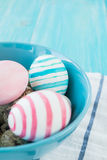 Colorful equal and chicken Easter Eggs on the blue rustic wooden background with towel. Selective focus. Royalty Free Stock Images