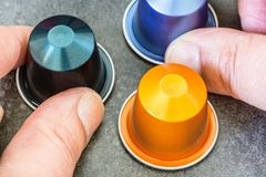 Colorful espresso coffee doses in hand. Closeup of colorful espresso coffee doses in hand royalty free stock photos