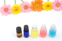 Colorful essential oil and flowers Stock Photos
