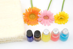 Colorful essential oil and yellow towel. Essential oil and yellow towel with gerbera daisy on white background Royalty Free Stock Images