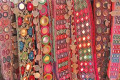 Colorful ethnic belts with mirrors at market in GOA, India. Tibetan souvenirs.  royalty free stock photos
