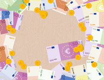 Colorful euro banknotes and euro coins on a wood background. Royalty Free Stock Images