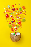 Colorful explosion of candies in coconut on yellow colored background, creative still life, flat lay style. Royalty Free Stock Photography