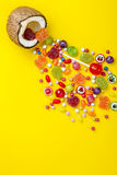 Colorful explosion of candies in coconut on yellow colored background, creative still life, flat lay style. Colorful explosion of candies in coconut on yellow stock images